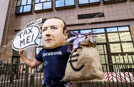 An activist wearing a mask depicting Facebook's CEO Mark Zuckerberg holds a banner reading 'Tax me' at the start of an European Union Finance Ministers Meeting in front of the European Council in Brussels, Belgium, 04 December 2018. Activists ask for an EU tax on big digital firms.