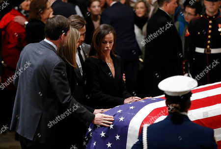 Stock Photo of Barbara Bush, Jenna Bush Hager, Craig Coyne, Henry Hager. Barbara Bush, from right, granddaughter of President George H.W. Bush, her husband Craig Coyne, sister Jenna Bush Hager, and husband Henry Hager, rest their hands on the flag-draped casket of former President George H.W. Bush as he lies in state in the Capitol Rotunda in Washington