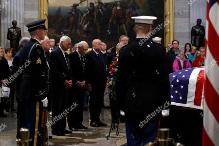 Former Secretary of State Colin Powell stands alongside former Operation Desert Storm commanders in front of the flag-draped casket of former President George H.W. Bush as he lies in state in the Capitol Rotunda in Washington