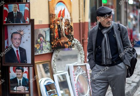 A man walks near pictures of Turkish President Recep Tayyip Erdogan (L-middle), Devlet Bahceli (L-up), the leader of the Nationalist Movement Party (MHP), and Former Turkish President Turgur Ozal (L-down) in Istanbul, Turkey, 04 December 2018.