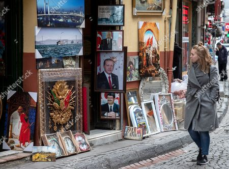 A woman walks near pictures of Turkish President recep tayyip Erdogan (L-middle), Devlet Bahceli (L-up), the leader of the Nationalist Movement Party (MHP) and Former Turkish President Turgur Ozal (L-down) in Istanbul, Turkey, 04 December 2018.