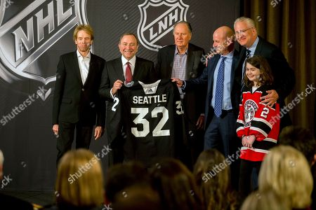NHL commissioner Gary Bettman, center left, holds a jersey after the NHL Board of Governors announced Seattle as the league's 32nd franchise, in Sea Island Ga.. Joining Bettman, from left to right, is Jerry Bruckheimer, David Bonderman, David Wright, Tod Leiweke and Washington Wild youth hockey player Jaina Goscinski