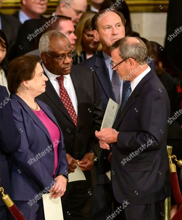 Chief Justice of the United States John G Roberts Jnr, Jr., right, converses with, from left, Associate Justice of the Supreme Court Elena Kagan, Associate Justice of the Supreme Court Clarence Thomas, and Associate Justice of the Supreme Court Samuel A. Alito, Jr. prior to the ceremony honoring former United States President George H.W. Bush, who will Lie in State in the Rotunda of the US Capitol.