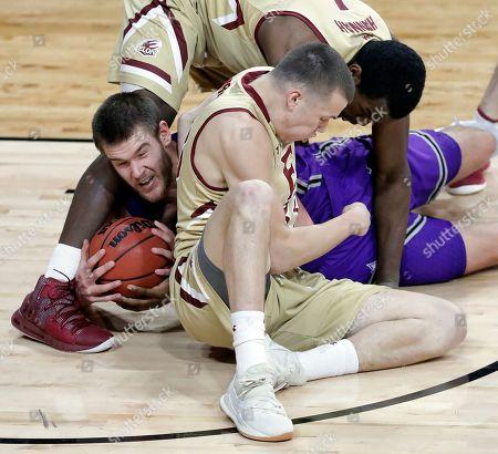 Furman's Matt Rafferty, center, holds onto the ball as the battles Elon's Chuck Hannah, top, and Simon Wright, bottom, in the second half of an NCAA college basketball game in Elon, N.C