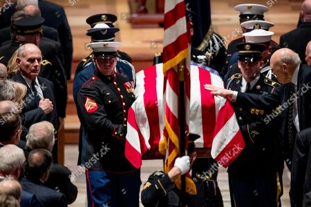 US President Donald Trump's Chief of Staff John Kelly, left, watches as Former Sen. Alan Simpson, R-Wyo, right, touches the flag-draped casket of former US President George H.W. Bush as it is carried out by a military honor guard during a State Funeral at the National Cathedral, in Washington, DC, USA, 05 December 2018. George H.W. Bush, the 41st President of the United States (1989-1993), died at the age of 94 on 30 November 2018 at his home in Texas.