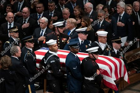 George W. Bush, Laura Bush, Michelle Obama Barack Obama, Jummy Carter Rosalynn Carter, Bill Clinton, Hillary Clinton, Donald Trump Melania Trump. The flag-draped casket of former President George H.W. Bush is carried by a military honor guard past former President George W. Bush and wife Laura Bush, President Donald Trump, first lady Melania Trump, former President Barack Obama, Michelle Obama, former President Bill Clinton, former Secretary of State Hillary Clinton and former President Jimmy Carter during a State Funeral at the National Cathedral, in Washington