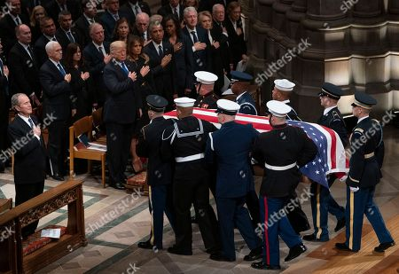 George W. Bush, Donald Trump, Melania Trump, Rosalynn Carter, Barack Obama, Michelle Obama, Hillare Clinton, Bill Clinton, Jiimmyb Carter. The flag-draped casket of former President George H.W. Bush is carried by a military honor guard past former President George W. Bush, President Donald Trump, first lady Melania Trump, former President Barack Obama, Michelle Obama, former President Bill Clinton, former Secretary of State Hillary Clinton, former President Jimmy Carter, and Rosalynn Carter at the end of a State Funeral at the National Cathedral, in Washington