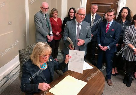 Oklahoma Gov. Mary Fallin speaks, in Oklahoma City, while members of her staff look on after she signed one of 21 prison commutations for mostly female inmates convicted of drug crimes