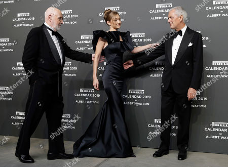 Model Gigi Hadid, center, is flanked by photographer Albert Watson, left, and Pirelli CEO, Marco Tronchetti Provera, on the occasion of the 2019 Pirelli Calendar event in Milan, Italy