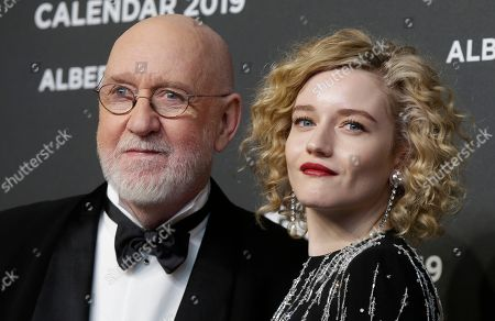 Actress Julia Garner is flanked by photographer Albert Watson on the occasion of the 2019 Pirelli Calendar event in Milan, Italy
