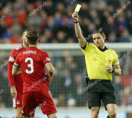 Referee Steven McLean shows a yellow card to Graeme Shinnie of Aberdeen for a challenge on Gareth McAuley of Rangers