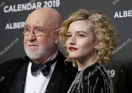 Photographer Albert Watson, left, is flanked by actress Julia Garner, on the red carpet on the occasion of the 2019 Pirelli Calendar event in Milan, Italy