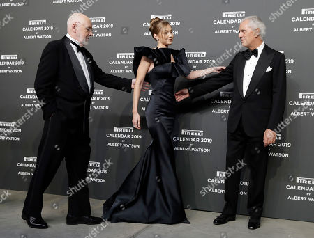 Model Gigi Hadid, center, is flanked by photographer Albert Watson, left, and Pirelli CEO Marco Tronchetti Provera on the red carpet on the occasion of the 2019 Pirelli Calendar event in Milan, Italy