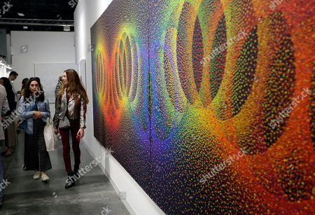 """People walk past a painting by Julio Le Parc titled """"Alchimie 396"""" displayed at the Nara Roesler Gallery at Art Basel, in Miami Beach, Fla. Over 200 modern and contemporary art galleries from around the world are displaying artworks. The show runs Dec. 6-9"""