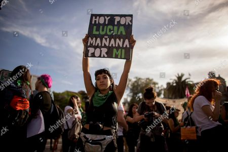 """A woman holds up a sign that reads in Spanish: """"Today for Lucia. Tomorrow for me,"""" referring to gender violence victim Lucia Perez, during a protest against gender violence in Buenos Aires, Argentina, . Argentine feminist groups and labor unions are protesting a court ruling that acquitted two men accused of sexually abusing and killing the 16-year-old girl"""