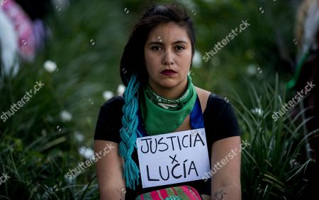 """A woman wears a sign that reads in Spanish: """"Justice for Lucia,"""" referring to gender violence victim Lucia Perez, during a protest against gender violence in Buenos Aires, Argentina, . Argentine feminist groups and labor unions are protesting a court ruling that acquitted two men accused of sexually abusing and killing the 16-year-old girl"""
