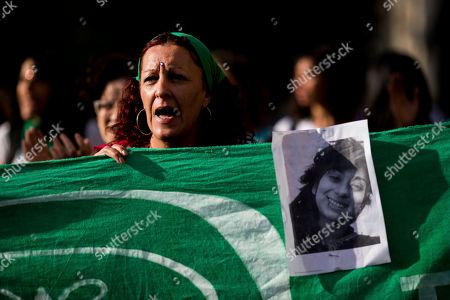 A pictures of gender violence victim Lucia Perez, 16, is held up during a protest in Buenos Aires, Argentina, . Argentine feminist groups and labor unions are protesting the court ruling that acquitted two men accused of sexually abusing and killing the teen. The ruling said that the girl had consensual sex with one of the men and that she died of an overdose