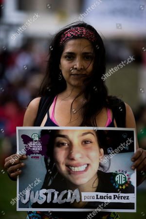 """Stock Image of A woman holds a photo of gender violence victim Lucia Perez, 16, carrying the Spanish message: """"Justice for Lucia Perez, during a protest in Buenos Aires, Argentina, . Argentine feminist groups and labor unions are protesting the court ruling that acquitted two men accused of sexually abusing and killing the teen. The ruling said that the girl had consensual sex with one of the men and that she died of an overdose"""