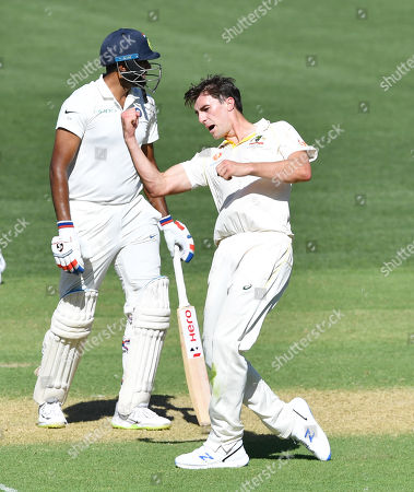 Patrick Cummins (R) of Australia reacts sfter the dismissal of Ravichandran Ashwin of India during day one of the first Test match between Australia and India at the Adelaide Oval in Adelaide, Australia, 06 December 2018.