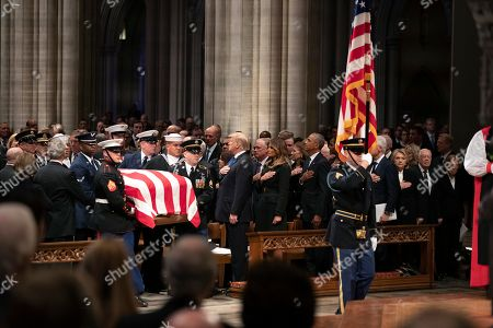 The flag-draped casket of former President George H.W. Bush is carried by a military honor guard past former President George W. Bush, left side, President Donald Trump, first lady Melania Trump, former President Barack Obama, Michelle Obama, former President Bill Clinton, former Secretary of State Hillary Clinton, former President Jimmy Carter, and Rosalynn Carter during a State Funeral at the National Cathedral.