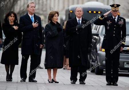 From right, former President George W. Bush, second from right, former first lady Laura Bush, Neil Bush and Sharon Bush, stand as the flag-draped casket of former President George H.W. Bush is carried by a joint services military honor guard from the U.S. Capitol.