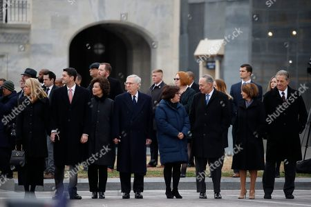 Stock Photo of Capitol Hill leadership from left, Speaker of the House Paul Ryan and his wife Janna Ryan, Senate Majority Leader Mitch McConnell and his wife Sec. of Transportation Elaine Chao, Senate Minority Leader Chuck Schumer and his wife Iris Weinshall and House Minority Leader Nancy Pelosi and her husband Frank Pelosi, stand just prior to the flag-draped casket of former President George H.W. Bush being carried out of the Capitol by a joint services military honor guard from the U.S. Capitol.
