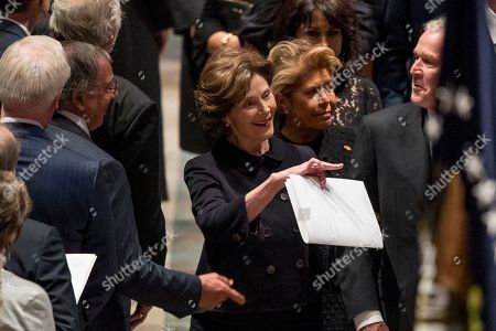 Former Defense Secretary Leon Panetta, left, greets former President George Bush, right, as he and his wife, former first lady Laura Bush follow the flag-draped casket of former President George H.W. Bush as it is carried out by a military honor guard during a State Funeral at the National Cathedral. Also pictured is Columba Bush, the wife of former Florida Gov. Jeb Bush, second from right.