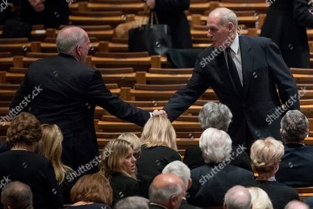 Former CIA Director John O. Brennan, left, shakes hands with President Donald Trump's Chief of Staff John Kelly, right, before a State Funeral the National Cathedral.