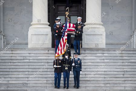 The flag-draped casket of former President George H. W. Bush is carried by a joint services military honor guard down the steps of the U.S. Capitol.