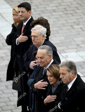 Congressional leaders from left to right, Speaker of the House Paul Ryan, R-Wis, Senate Majority Leader Mitch McConnell, R-Ky., Senate Minority Leader Chuck Schumer, D-NY, and House Minority Leader Nancy Pelosi, D-Calif., watch as a U.S. military honor guard carries the flag-draped casket of former U.S. President George H. W. Bush from the U.S. Capitol