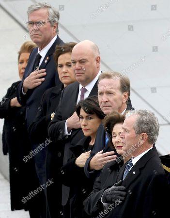 Former U.S. President George W. Bush, right, his wife Laura Bush, second from right, and brother Jeb Bush, second from left, watch as a U.S. military honor guard carries the flag-draped casket of former President George H.W. Bush from the U.S. Capitol