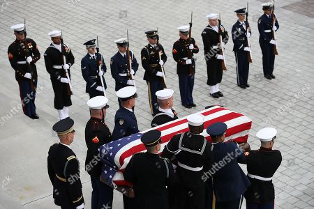 A U.S. military honor guard team carries the flag draped casket of former U.S. President George H. W. Bush from the U.S. Capitol