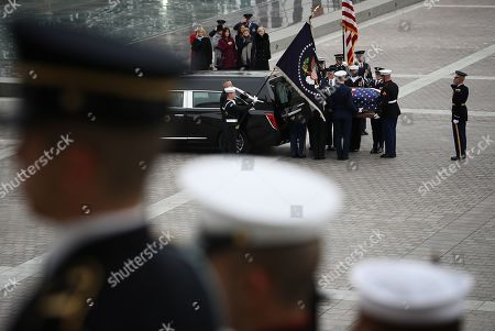 A U.S. military honor guard team places the flag draped casket of former U.S. President George H. W. Bush into a hearse on the east plaza of the U.S. Capitol