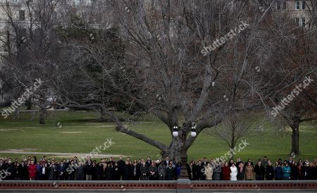 Spectators watch as a U.S. military honor guard team carries the flag draped casket of former U.S. President George H. W. Bush from the U.S. Capitol