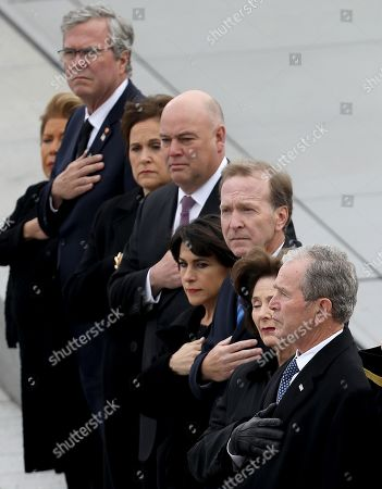 Former U.S. President George W. Bush (R) and his wife Laura Bush watch as a U.S. military honor guard team carries the flag draped casket of former U.S. President George H. W. Bush from the U.S. Capitol