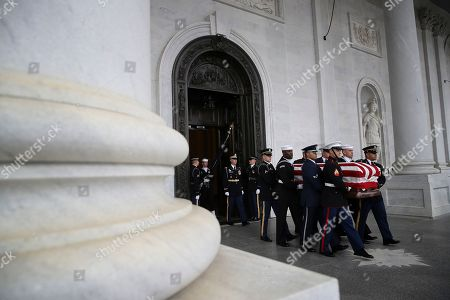 The flag-draped casket of former President George H. W. Bush is carried by a joint services military honor guard out of the Capitol.