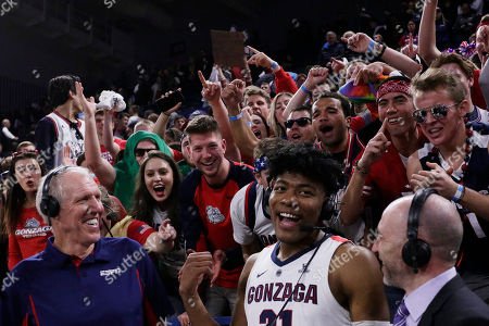 ESPN announcers Bill Walton, left, and Dave Pasch, right, interview Gonzaga forward Rui Hachimura as fans cheer after an NCAA college basketball game between Gonzaga and Washington in Spokane, Wash