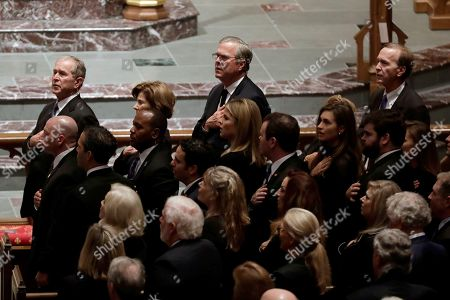 Former President George W. Bush, left, and his brothers former Florida Gov. Jeb Bush and Neil Bush, sing during a funeral for former President George H.W. Bush at St. Martin's Episcopal Church, in Houston