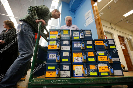Locked boxed of ballots are moved by Tom Bull during the first day of the recount in Maine's 2nd Congressional District, in Augusta, Maine. The recount was requested by outgoing U.S. Rep. Bruce Poliquin after losing a November ranked-choice race to Rep.-elect Jared Golden