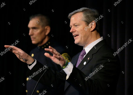 Frederick Ryan, Charlie Baker. Massachusetts Gov. Charlie Baker, right, addresses an audience as Arlington, Mass., Police Chief Frederick Ryan, left, looks, in Boston, during a national summit focused on police efforts to address the opioid epidemic