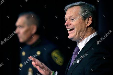 Massachusetts Gov. Charlie Baker, right, addresses an audience as Arlington, Mass., Police Chief Frederick Ryan, left, looks, during a national summit focused on police efforts to address the opioid epidemic at Harvard Medical School, in Boston