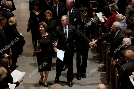 Former President George W. Bush and former first lady Laura Bush walk down the isle during a funeral for former President George H.W. Bush at St. Martin's Episcopal Church, in Houston