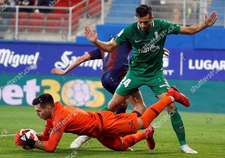 SD Eibar's Alex Perez (C) in action against Sporting Gijon's goalkeeper Dani Martin (L) during a Spanish King's Cup round of 32 second leg match between SD Eibar and Sporting Gijon at the Ipurua stadium in Eibar, northern Spain, 06 December 2018.