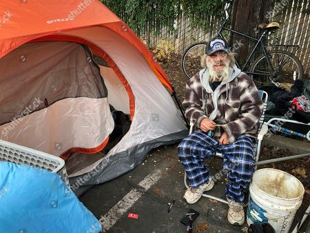 Steve Wilson poses for a photo next to the tent where he's been sleeping in the parking lot of an abandoned Toys R Us in Chico, Calif. Wilson, who was homeless in Chico before the worst wildfire in California history destroyed nearby Paradise, has seen the streets grow more crowded with homeless people