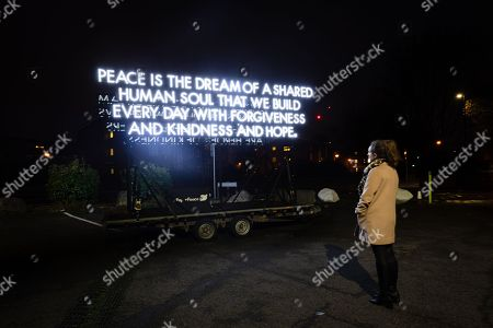 A woman looks at a striking mobile 14 foot high illuminated and double sided 'Peace Poem' by artist and poet, Robert Montgomery arrives at Rothbury Hall in Greenwich, where it will be on display for visitors until 13th December 2018 following a countrywide tour.