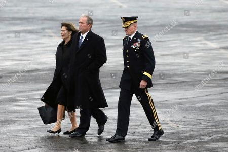 Former President George W. Bush and former first lady Laura Bush walk to observe the departure ceremony as the flag-draped casket of former President George H.W. Bush is carried by a joint services military honor guard to a train at Union Pacific Westfield auto facility, in Spring, Texas