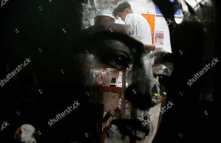 Stock Picture of An artist makes screen prints in the background of Frida Kahlo's face printed on the art installation from artists, Rirkrit Tiravanija and Tomas Vu, at the Untitled Art gallery during Art Basel, in Miami Beach, Fla. Over 200 modern and contemporary art galleries from around the world are displaying artworks