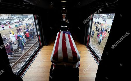 People pay their respects as the train carrying the casket of former President George H.W. Bush passes, along the route from Spring to College Station, Texas