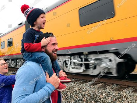 Ryder Davis, 3, watches the memorial train for President George H.W. Bush pass through Pinehurst, Texas, atop the shoulders of his father, 27-year-old Matthew Davis, on Thursday, in Pinehurst, Texas. On Thursday, that same 4,300-horsepower machine left a suburban Houston railyard loaded with Bush's casket for his final journey after almost a week of ceremonies in Washington and Texas