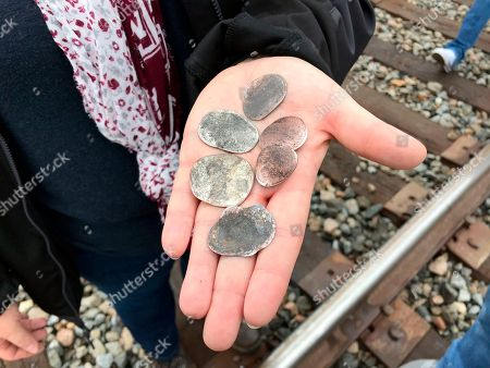 Ana Garza, of Cypress, Texas, displays coins flattened by the memorial train carrying the casket of President George H.W. Bush when it passed through Pinehurst, Texas, . On Thursday, that same 4,300-horsepower machine left a suburban Houston railyard loaded with Bush's casket for his final journey after almost a week of ceremonies in Washington and Texas